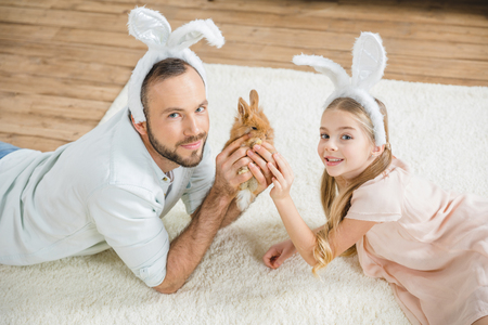Father and daughter playing with rabbit Stock Photo