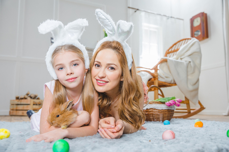 Mother and daughter playing with rabbit Stock Photo