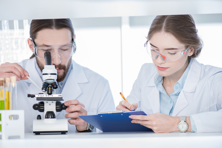 Chemists working with microscope