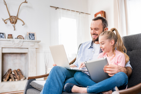 Father and daughter using devices Stock Photo
