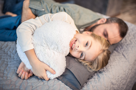 Father and daughter lying on bed