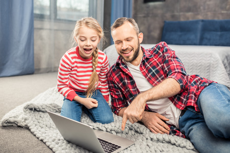 Father and daughter using laptop Stock Photo