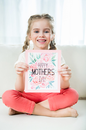 girl showing happy mothers day postcard in hands, mothers day concept