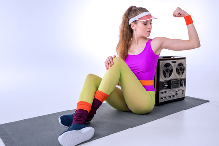 sporty woman showing muscles while sitting on mat
