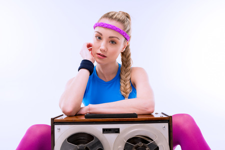 woman in fitness clothing sitting near retro record player