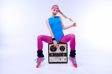excited woman in fitness clothing sitting on retro record player Imagens