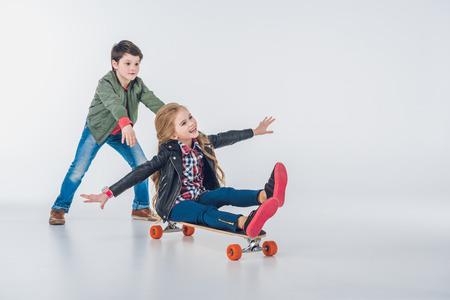 boyhood: Happy boy and girl having fun with skateboard