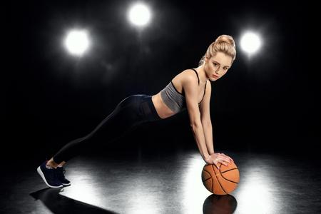 Aantrekkelijke sportvrouw in plank positie met basketbalbal