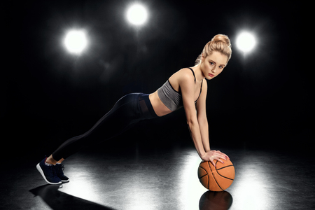 attractive sportswoman in plank position with basketball ball Stock Photo