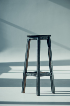 stool: View of wooden bar stool with shadows on grey