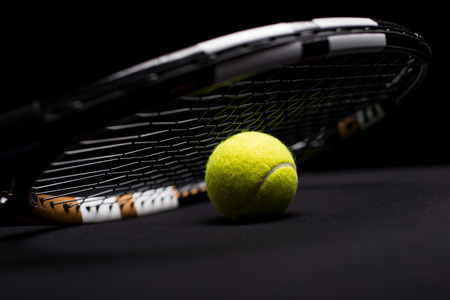 Close-up view of tennis ball and racquet  on black