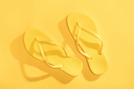 Close-up top view of comfortable yellow flip-flops on yellow background