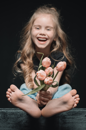laughing girl holding tulips bouquet on black