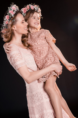 happy mother and daughter in floral wreaths and pink dresses