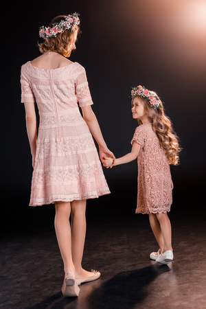 mother and daughter in floral wreaths holding hands