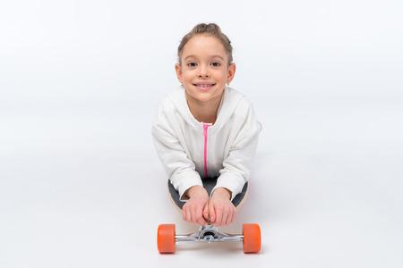 smiling girl lying on skateboard on white