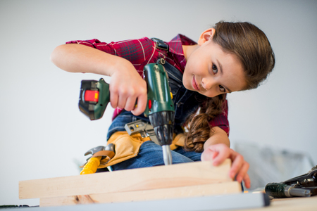 laboring: Girl drilling plank Stock Photo