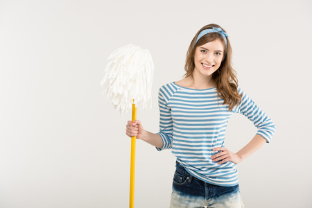 Attractive young woman with hand on waist holding mop and smiling at camera