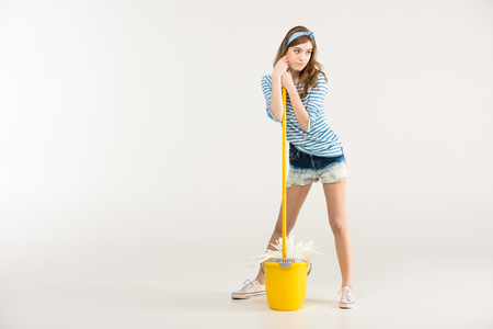 Beautiful young woman with mop and bucket looking away Stock Photo