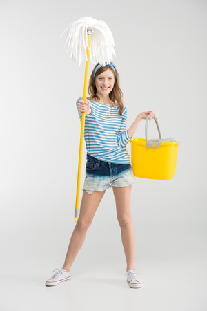 Beautiful young woman holding mop with bucket and smiling at camera