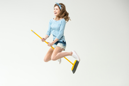 Young woman with broom Stock Photo