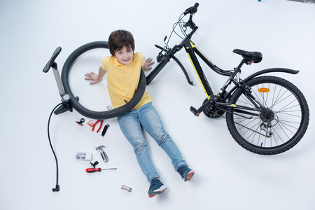 smiling boy sitting on floor near bicycle on white