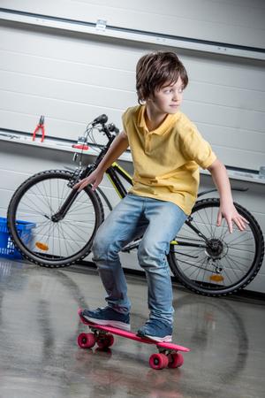 boyhood: boy with pink penny board, bicycle behind Stock Photo