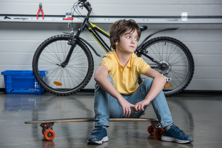 boyhood: little boy in t-shirt and jeans sitting on skateboard and looking away