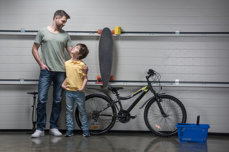 boyhood: father and son standing together in workshop with bicycle and skateboard