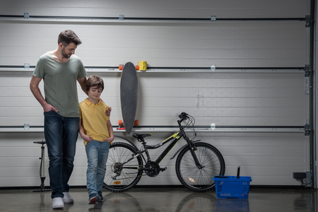 Father And Son Standing Together In Workshop With Bicycle And Skateboard  Stock Photo   76448523