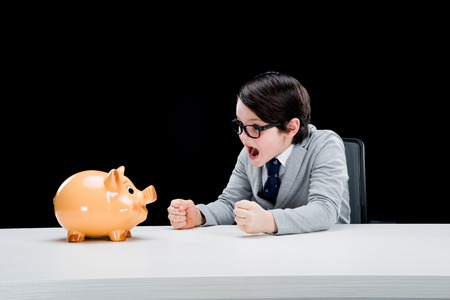 pre teen boy: boy businessman shouting at piggy bank Stock Photo