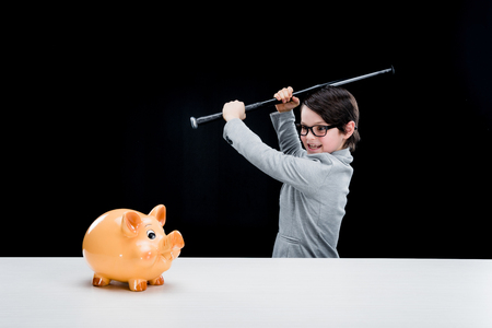 pre teen boy: boy in formal suit holding baseball bat hitting piggy bank