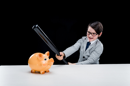 boy in formal suit holding baseball bat hitting piggy bank