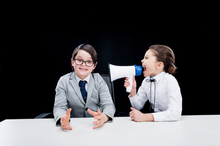 Boy and girl in formal wear interacting with bullhorn Stock Photo