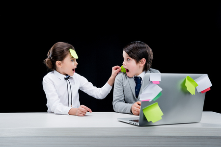boyhood: portrait of girl putting note on boys face at workplace