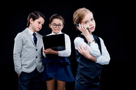 boyhood: Girl using smartphone with coworkers behind