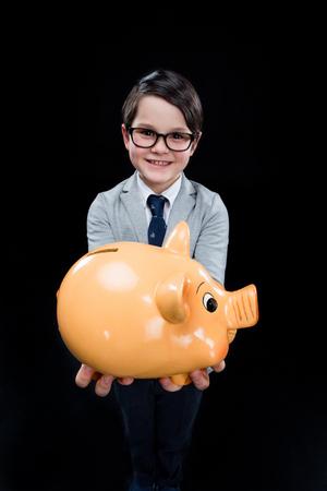boyhood: Adorable boy with piggy bank Stock Photo