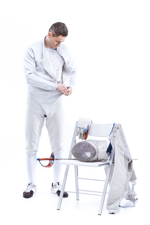 man professional fencer putting on protective costume on white Stock Photo
