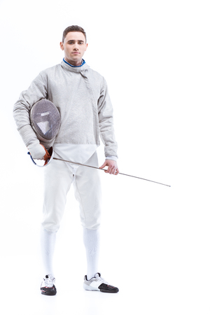 confident man professional fencer standing with helmet and rapier Stok Fotoğraf