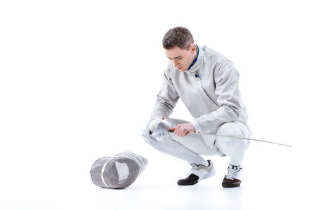 Young man professional fencer holding sword and crouching