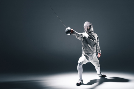 Professional fencer in fencing mask with rapier standing in position