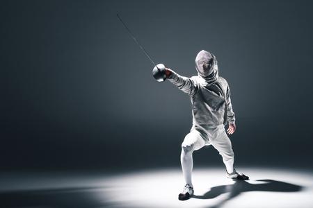 Esgrimista profesional en la máscara de esgrima con el estoque de pie en posición Foto de archivo - 76424528