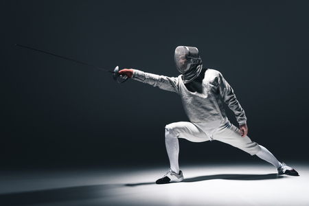 Professional fencer in fencing mask with rapier standing in position Imagens - 76424531