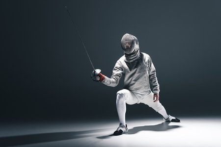 Professional fencer in fencing mask with rapier standing in position Imagens - 76424532