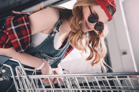 young woman with cap and sunglasses standing with shopping cart