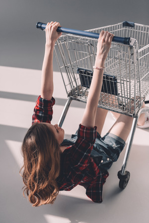 young woman in checkered shirt hanging on shopping cart
