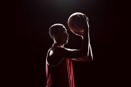 lighting background: African american basketball player throwing ball Stock Photo