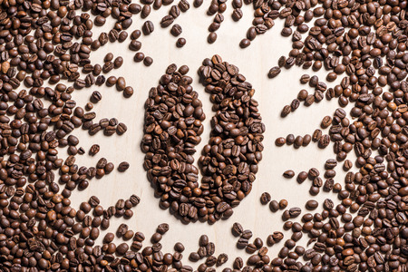 Close-up top view of coffee bean symbol made from roasted coffee grains
