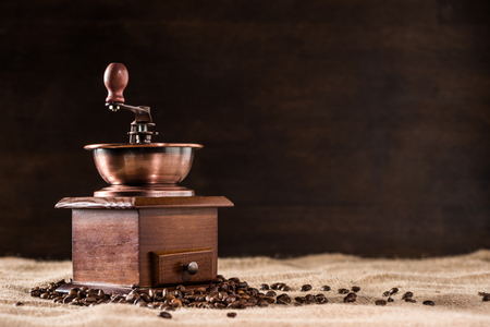 Coffee mill with aromatic coffee beans on scattered