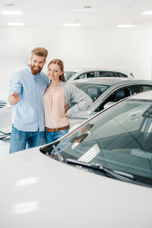 Happy couple choosing car in dealership salon, man pointing on car